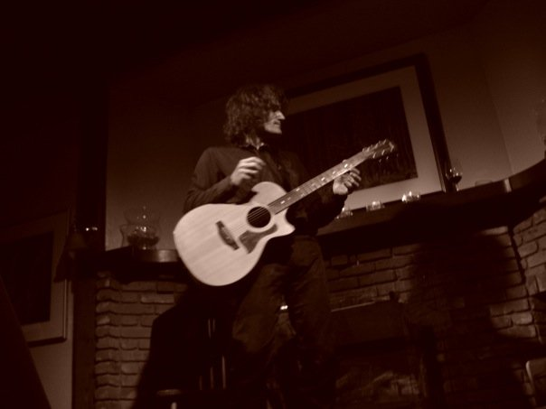 Steven Bates playing acoustic guitar